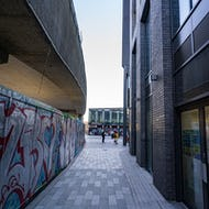 A walkway between graffiti and a modern office building